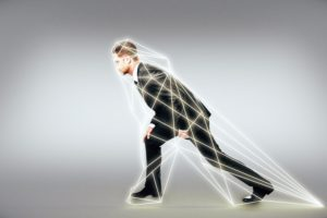 A man in a suit tries to stagger forward but a net of fibres holds him back