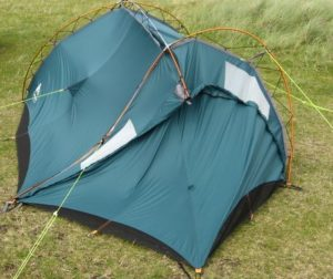 A small tent in a field, squashed on one side with bulges and pulls on the other
